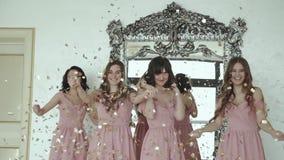 Meninas felizes no vestido de noite que gerencie ao redor e que joga acima envoltórios dentro filme