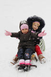 Meninas felizes nos panos do inverno que deslizam no pequeno trenó Imagens de Stock