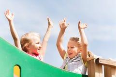 Meninas felizes que acenam as mãos no campo de jogos das crianças Foto de Stock