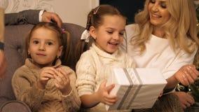 Meninas felizes que agitam um presente para supor o que é interno fotografia de stock royalty free