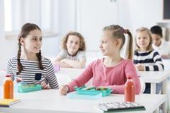 Meninas felizes que apreciam a ruptura na escola e que comem o café da manhã fotos de stock royalty free