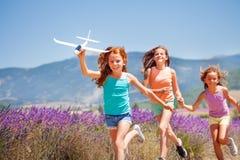 Meninas felizes que correm e que jogam com plano do brinquedo fotos de stock