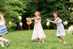 Meninas felizes que jogam o jogo da etiqueta na festa de anos Fotografia de Stock Royalty Free