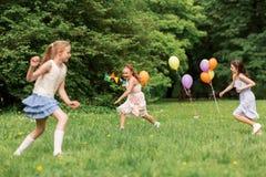 Meninas felizes que jogam o jogo da etiqueta na festa de anos Foto de Stock