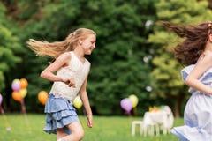 Meninas felizes que jogam o jogo da etiqueta na festa de anos Imagem de Stock