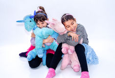Meninas felizes que mantêm brinquedos do unicórnio isolados no branco Foto de Stock