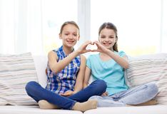 Meninas felizes que mostram o sinal da mão da forma do coração Fotos de Stock Royalty Free