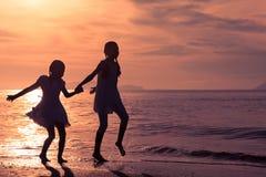 Meninas felizes que saltam na praia Fotografia de Stock