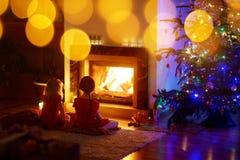 Meninas felizes que sentam-se por uma chaminé na Noite de Natal imagem de stock royalty free