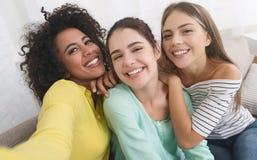Meninas felizes que tomam o selfie, tendo o divertimento em casa imagens de stock