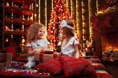 Meninas felizes que vestem a caixa de presente aberta dos pijamas do Natal por uma chaminé em uma sala de visitas escura acolhedo fotos de stock