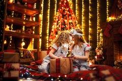 Meninas felizes que vestem a caixa de presente aberta dos pijamas do Natal por uma chaminé em uma sala de visitas escura acolhedo imagens de stock