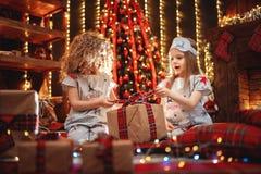 Meninas felizes que vestem a caixa de presente aberta dos pijamas do Natal por uma chaminé em uma sala de visitas escura acolhedo imagens de stock royalty free