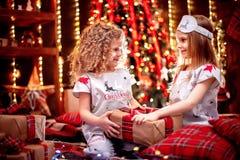 Meninas felizes que vestem a caixa de presente aberta dos pijamas do Natal por uma chaminé em uma sala de visitas escura acolhedo imagem de stock royalty free