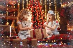 Meninas felizes que vestem a caixa de presente aberta dos pijamas do Natal por uma chaminé em uma sala de visitas escura acolhedo foto de stock royalty free