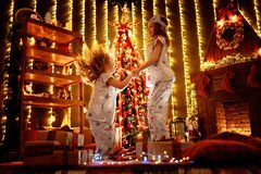Meninas felizes que vestem os pijamas do Natal que jogam por uma chaminé em uma sala de visitas escura acolhedor na Noite de Nata fotos de stock