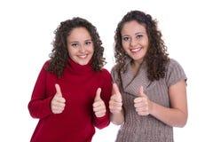 Meninas gêmeas felizes que fazem o polegar acima do gesto sobre o fundo branco Imagem de Stock Royalty Free