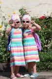 Meninas gêmeas pequenas bonitos que fazem V-sinais imagens de stock