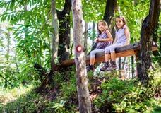 Meninas gêmeas que descansam e que sentam-se no banco nas madeiras Fotografia de Stock Royalty Free