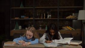 Meninas inteligentes que fazem trabalhos de casa para a escola primária filme