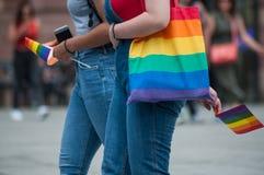 Meninas lésbicas que andam na rua com saco do arco-íris e em bandeiras do arco-íris antes do orgulho alegre foto de stock