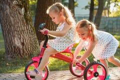 Meninas louras pequenas bonitos que montam uma bicicleta no verão Imagem de Stock