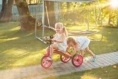 Meninas louras pequenas bonitos que montam uma bicicleta no verão Fotos de Stock Royalty Free