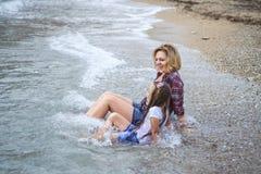 Meninas molhadas que sentam-se na água na praia do mar imagem de stock royalty free