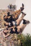 meninas multi-étnicos de sorriso novas que encontram-se no assoalho fotografia de stock