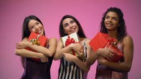 Meninas multirraciais nos pijamas que guardam presentes e que olham acima, feriados de espera filme