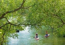 Meninas na canoa que remam em um canal na cidade Imagens de Stock