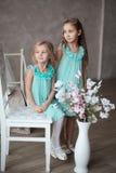 2 meninas no assento branco dos vestidos Imagens de Stock Royalty Free