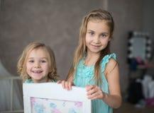 2 meninas no assento branco dos vestidos Imagem de Stock Royalty Free