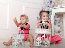 Meninas no assoalho com gaiolas de pássaro Fotografia de Stock