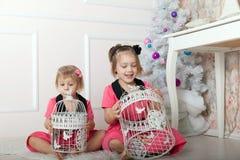 Meninas no assoalho com gaiolas de pássaro Imagens de Stock