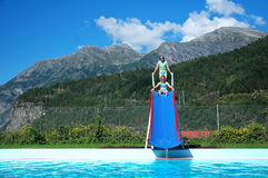 Meninas no auge da corrediça à piscina Imagens de Stock