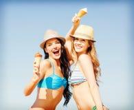 Meninas no biquini com gelado na praia Imagem de Stock