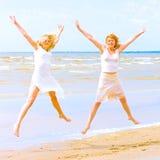 Meninas no branco que salta feliz em uma praia Fotografia de Stock