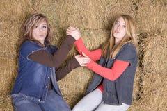 Meninas no monte de feno que tem o divertimento Foto de Stock Royalty Free