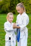 Meninas no quimono branco durante o karaté do treinamento imagem de stock royalty free
