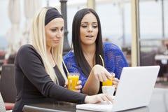 Meninas no restaurante com portátil Imagem de Stock