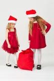 Meninas no sino Santa Claus que olha em um saco imagem de stock