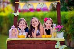 Meninas no suporte de limonada no jardim Imagens de Stock
