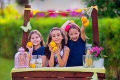 Meninas no suporte de limonada no jardim Fotografia de Stock Royalty Free