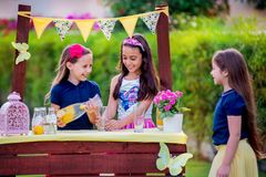 Meninas no suporte de limonada no jardim Imagem de Stock Royalty Free