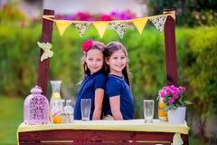 Meninas no suporte de limonada no jardim Imagem de Stock