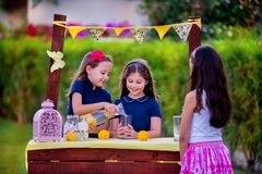 Meninas no suporte de limonada no jardim Fotografia de Stock