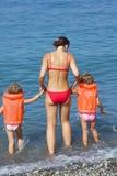 Meninas nos colete salva-vidas com a mulher que entra o mar fotografia de stock