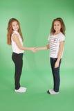 Meninas novas da escola que guardam as mãos e que sorriem na câmera Foto de Stock