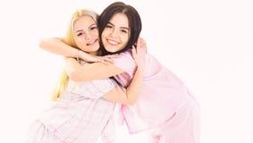 Meninas que abraçam firmemente, isolado no fundo branco Irmãs ou melhores amigos nos pijamas Conceito dos melhores amigos das irm imagem de stock